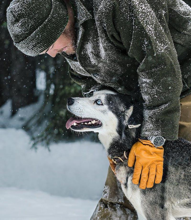 Filson Life - Elliot Anderson - Dogsledding dog with master in filson black coat and gloves