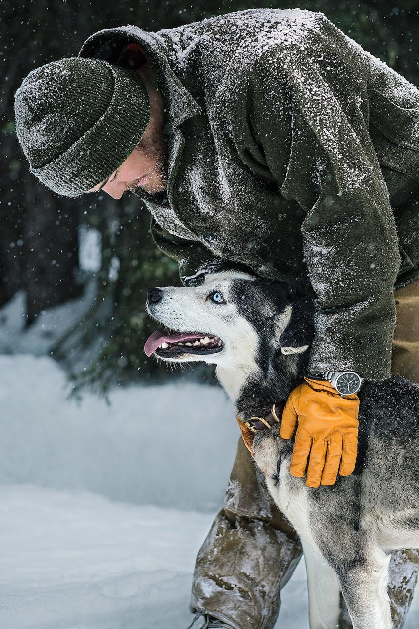 Man covered in snow wearing Filson clothing petting a husky.
