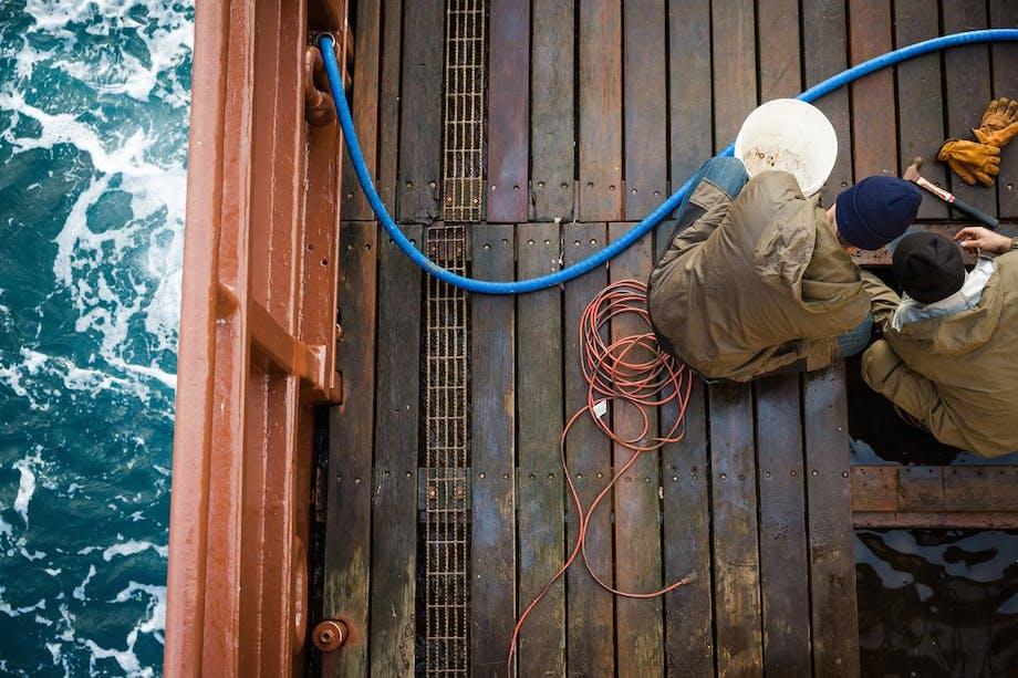 men in rain-proof brown jackets perform maintenance work on wooden deck at sea