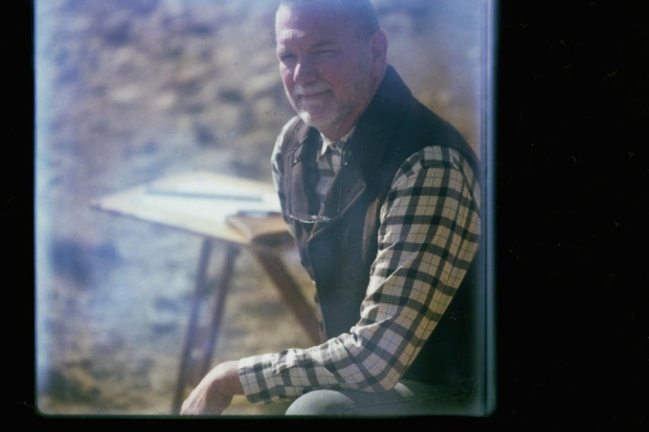 Eric Blinman, Archaeologist portrait through door window wearing vest and plaid shirt