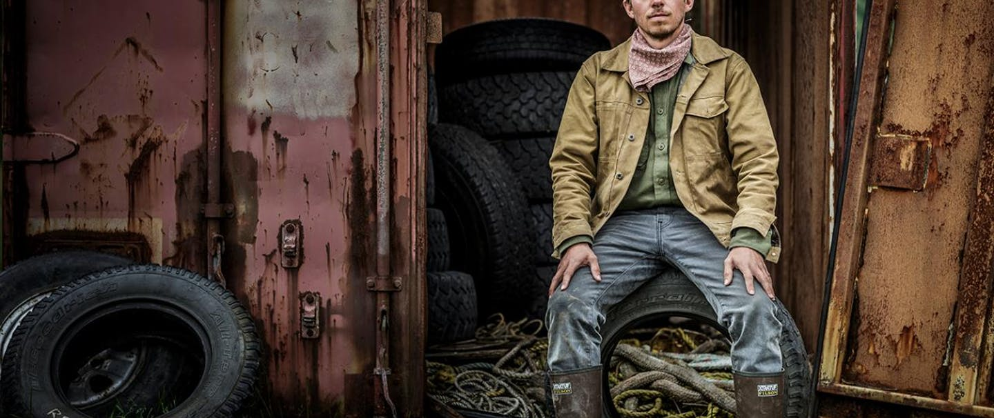 Wesley Larson sits on tire in brown jacket and waterproof boots