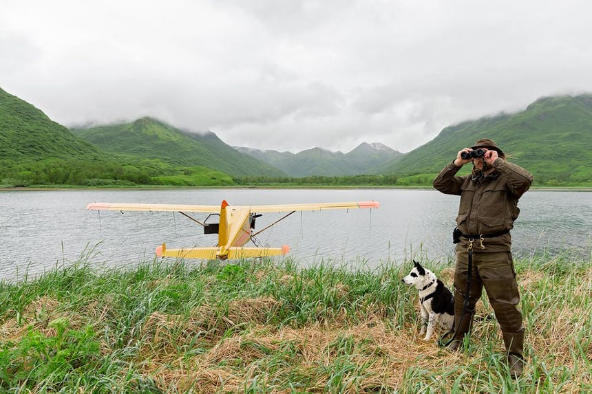 man in brown jacket and pants looking through binoculars next to dog with yellow seaplane on water