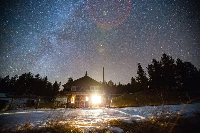 Filson Life - Upland Hunt Hannah Dewey log cabin and pine trees with milky way and sky full of stars in background