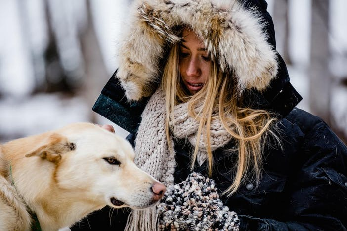 blonde woman wearing a navy coat with a fur lined hood and tan knit scarf petting a yellow lab