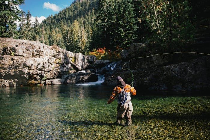 Man casting fly-fishing rod in clear water with waterfall and alpine ridge backdrop