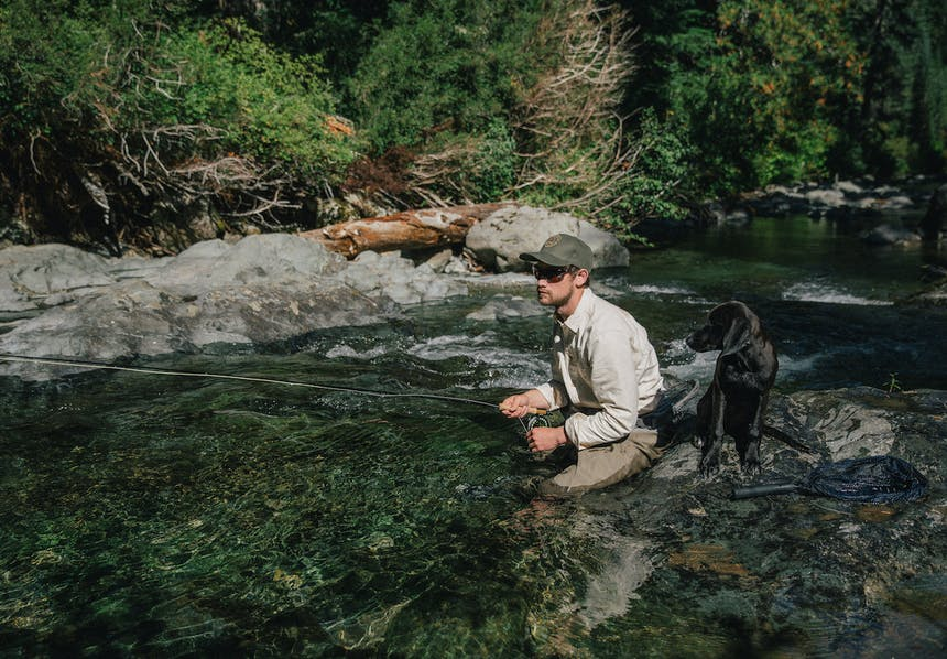 Man crouched in the middle of an alpine stream fly fishing alongside a dog to his right.