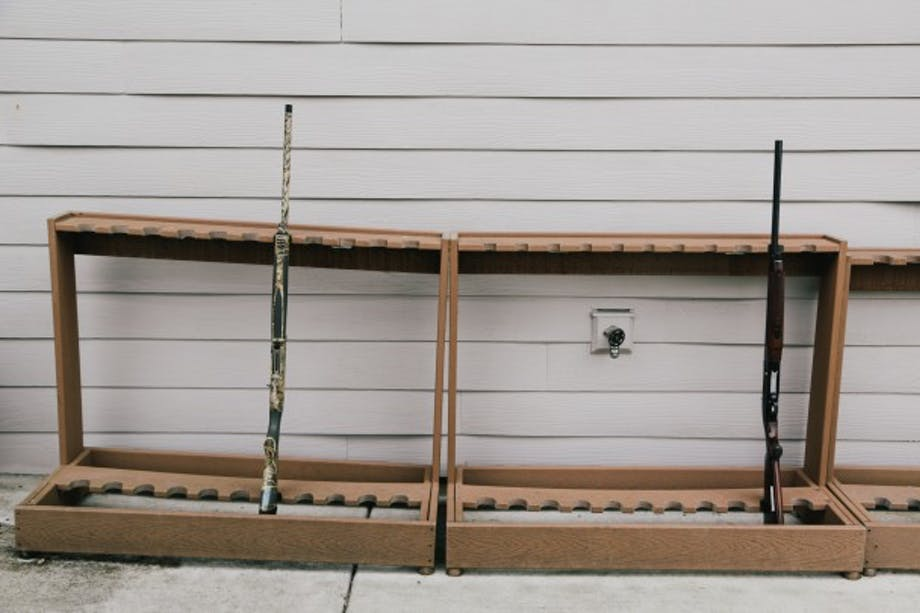 gun rack with two shotguns in front of wall with vinyl siding