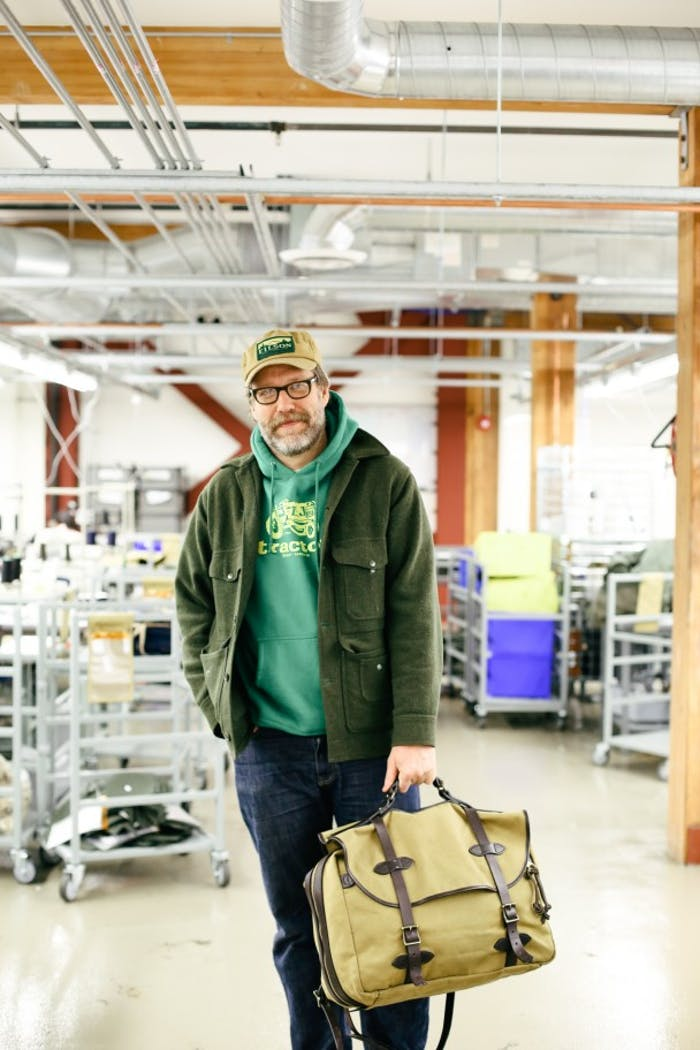 John Roderick holds filson briefcase in industrial workspace