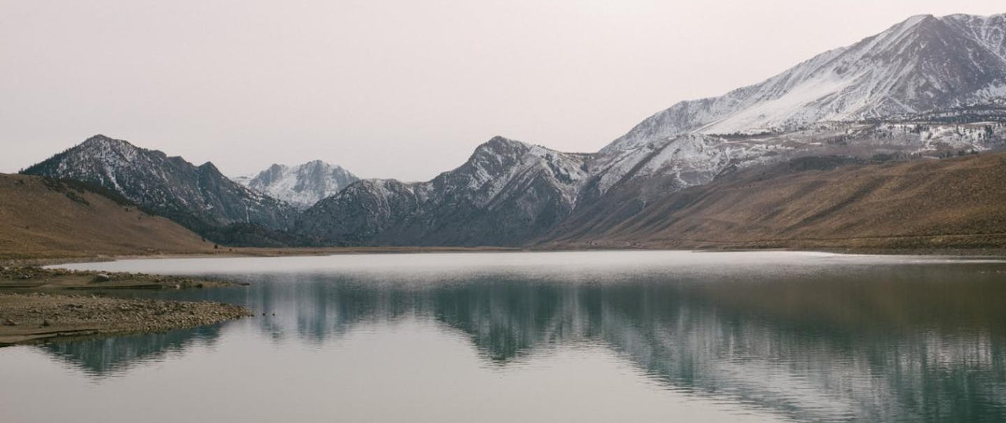 snow dusted mountains reflect in calm lake