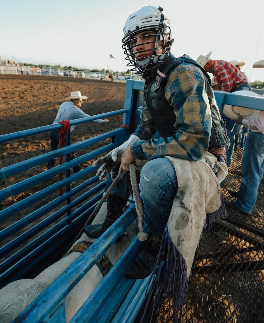 Garrett sitting on the fence ready to ride a bull