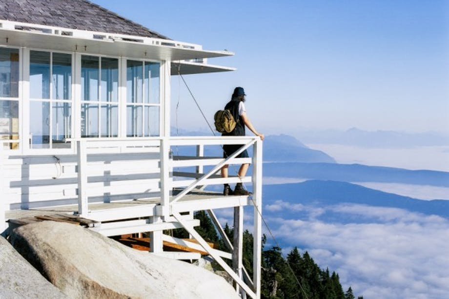person with filson pack stands on deck of high mountain lookout above clouds