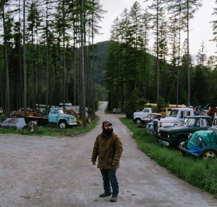 man standing in dirt road near classic cars on grass and woods