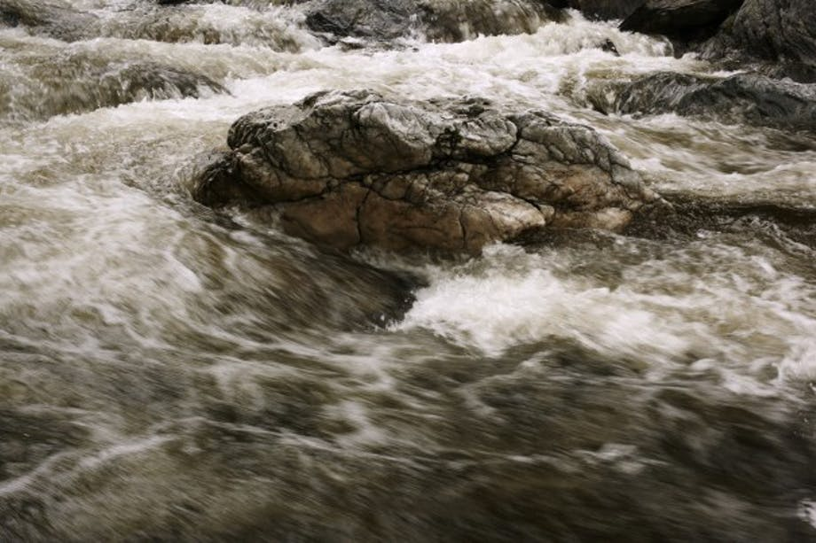 rushing river water with large central rock