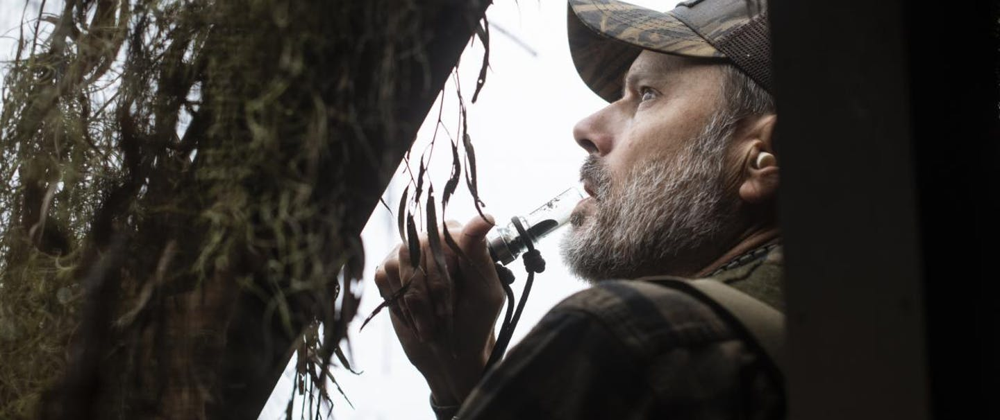 man looking out of a duck blind
