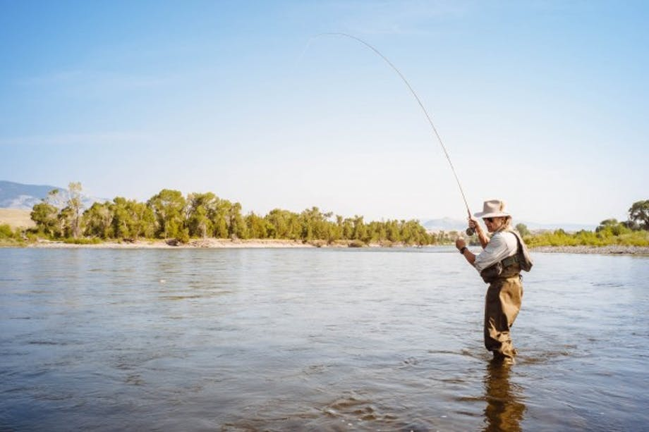Man with tensed fly fishing rod standing in lake