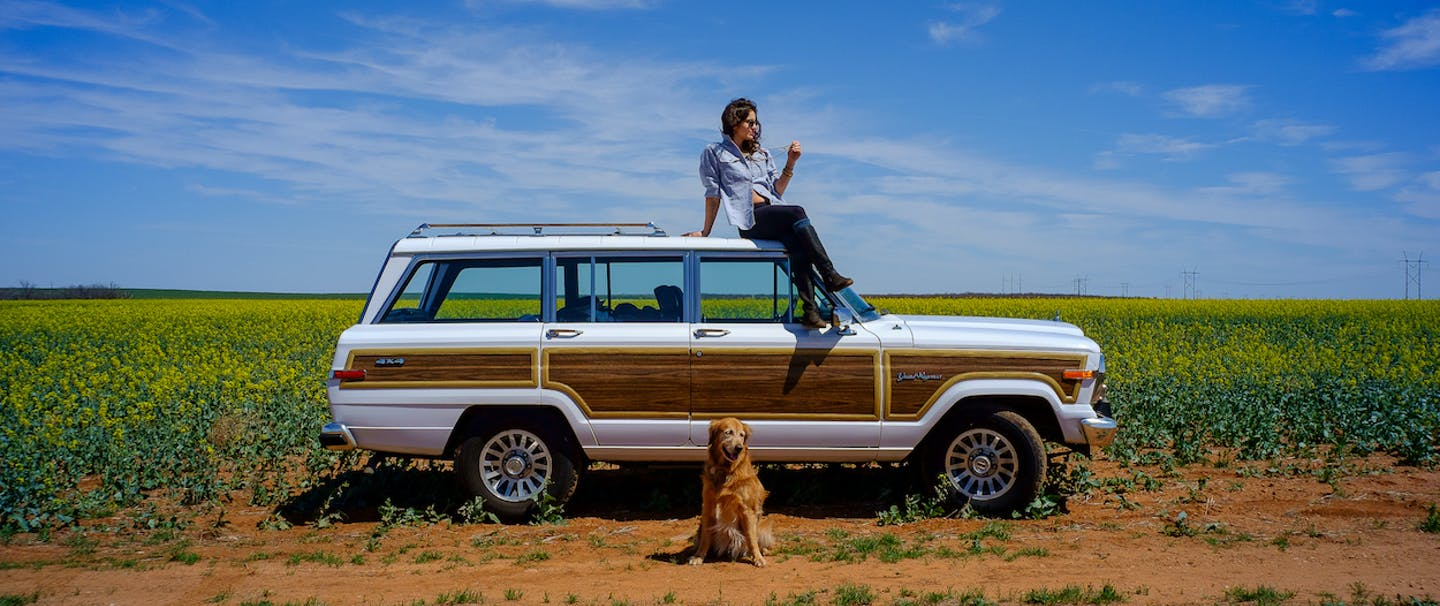 woman sitting on roof of white car in open green field with dog sitting on ground