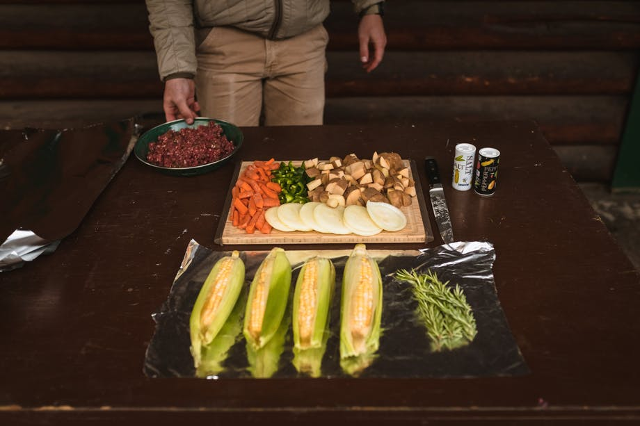 man prepping meal of veggies, corn, herbs, and meat at prep table