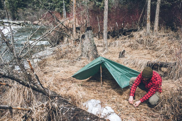building a tarp shelter among dead grasses and logs near river
