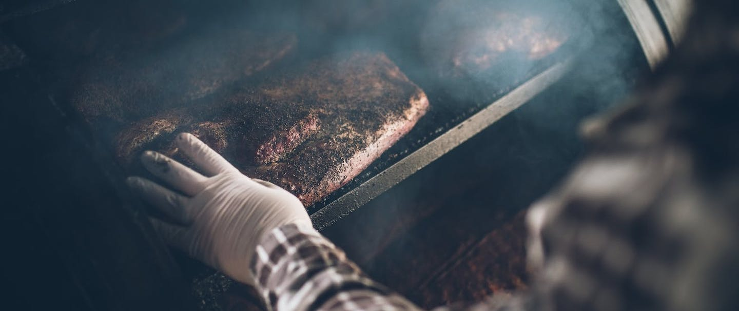 gloved hand touches meat in smoker