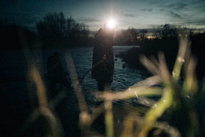 travis gillett in idaho silhouetted duck hunter stands in river at sunrise