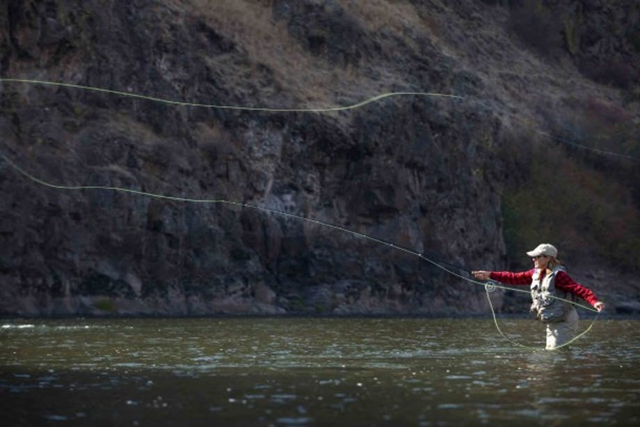 female fly fisher casts a long line standing in river with black cliff