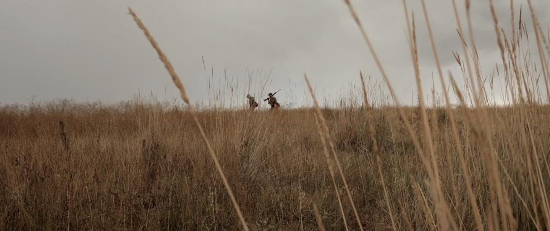 Greg-Reynolds hunters walk along ridge-line under overcast skies