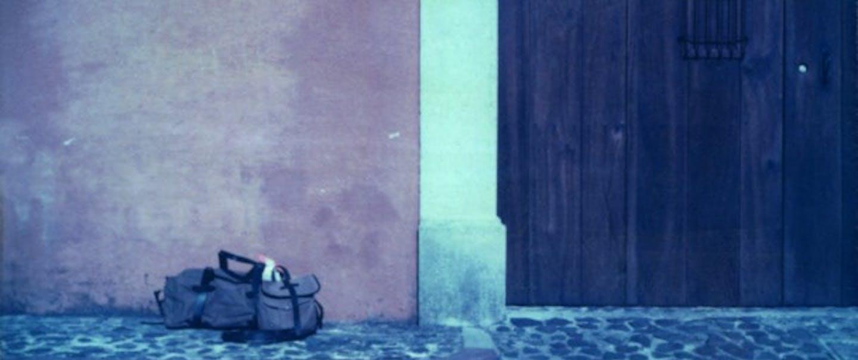 George Barnett; filson bags on black cobbles in front of wooden door