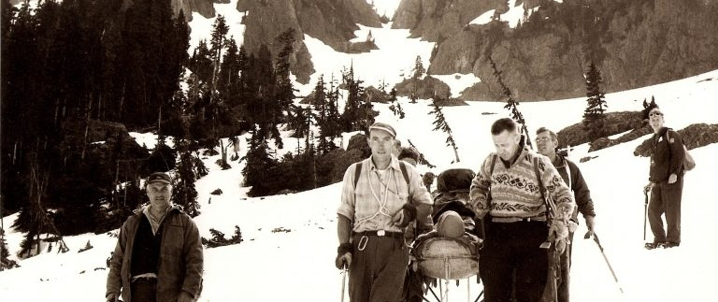 archival photo of seattle mountain rescue descending a mountain carrying an injured person