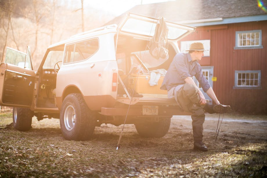 man removes waders and boots after flyfishing sitting on tailgate of his bronco
