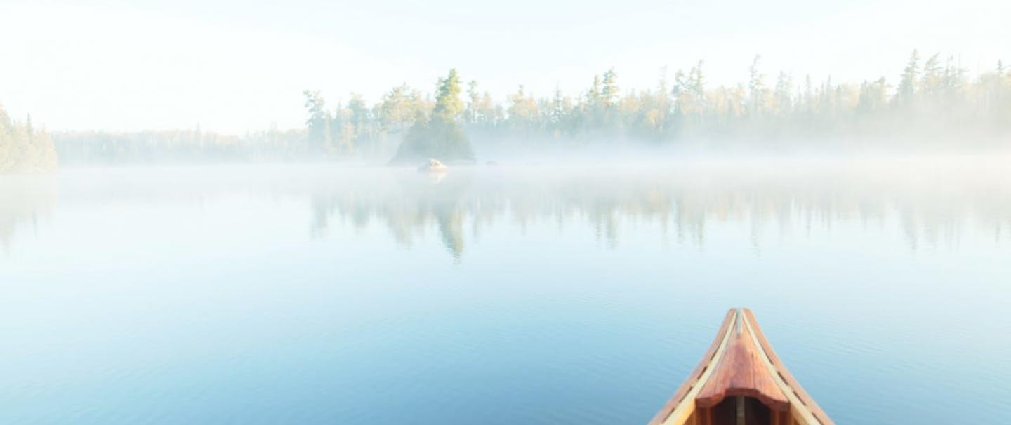 canoe on placid lake pointed toward fog covered forest
