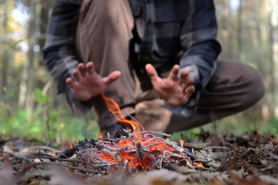 person warming hands behind burning kindling