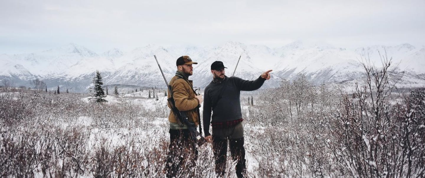 Two hunters with rifles point and look into the distance in a snowy field