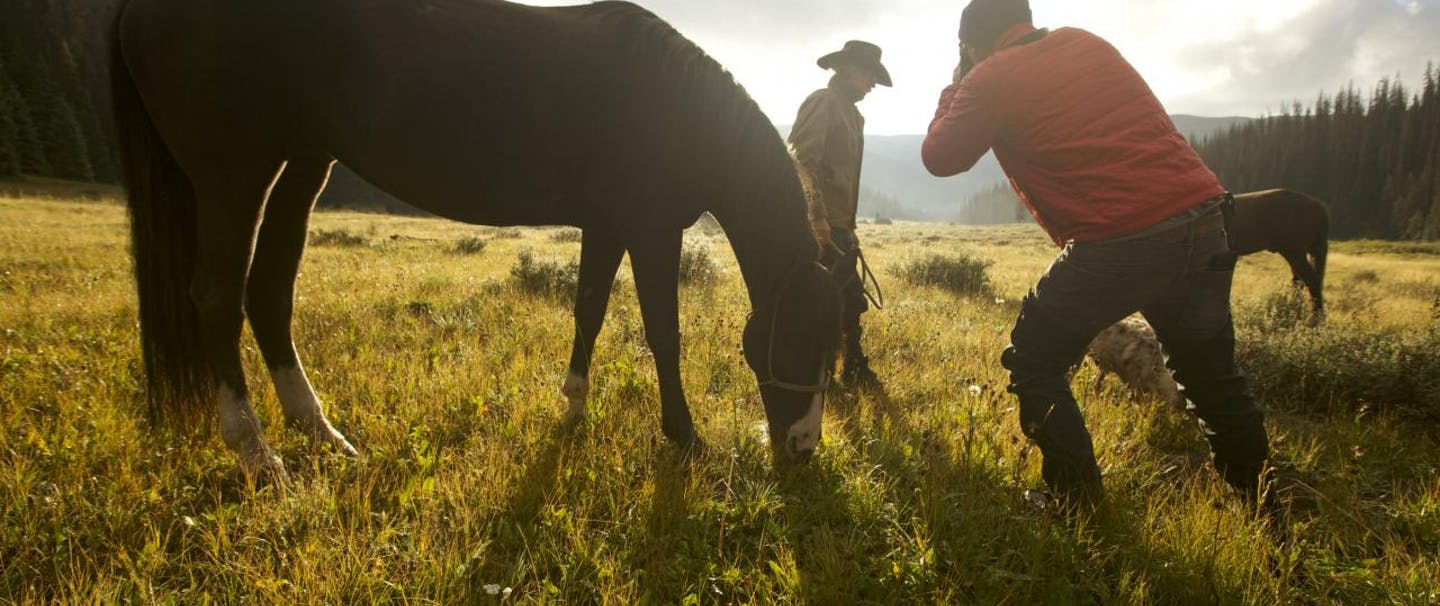 man takes picture of cowboy next to unsaddled horse forest clearing