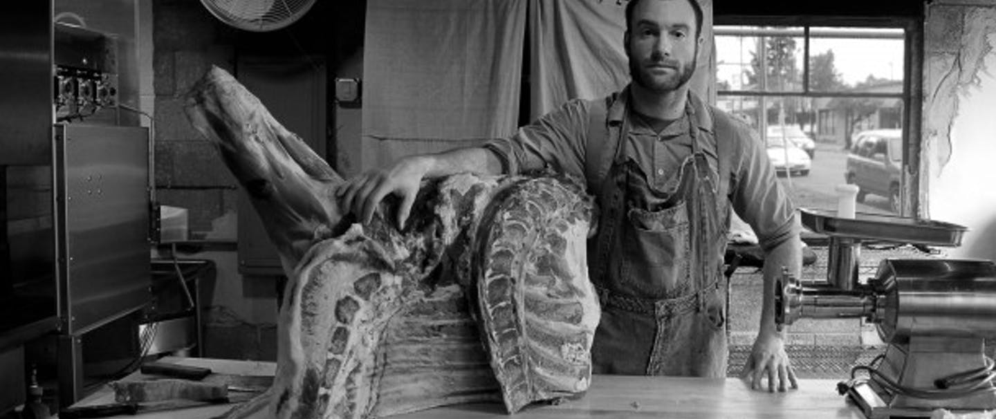 Trade Stories: Zeph, the Proletariat Butcher puts his arm on a large section of meat on a prep table