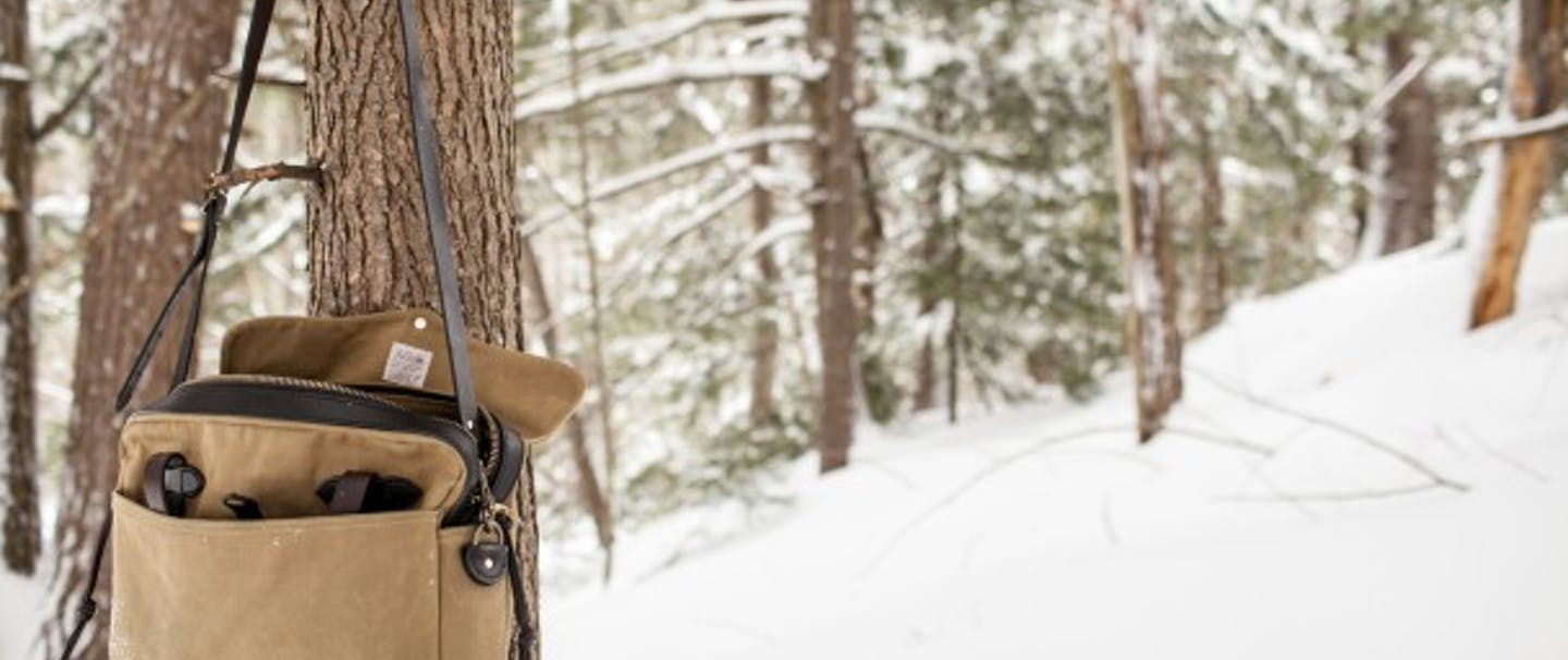 Beige filson bag hangs on a tree branch in snowy forest