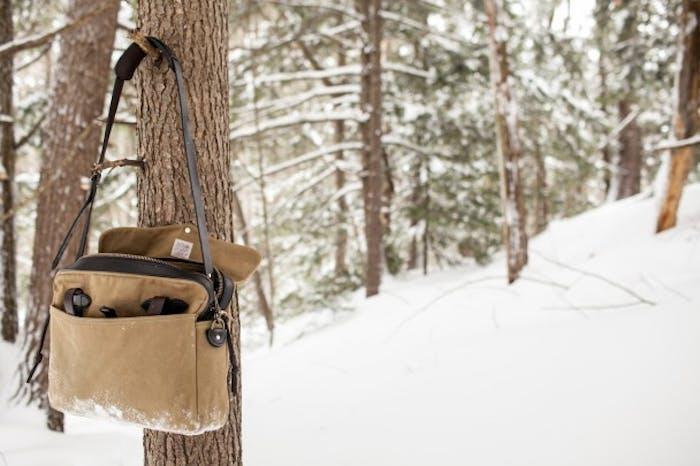 Beige filson bag hangs on a tree branch in snowy forest