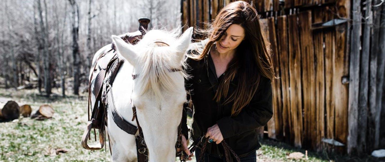 Jainee-Wylder leads bridled white horse next to barn