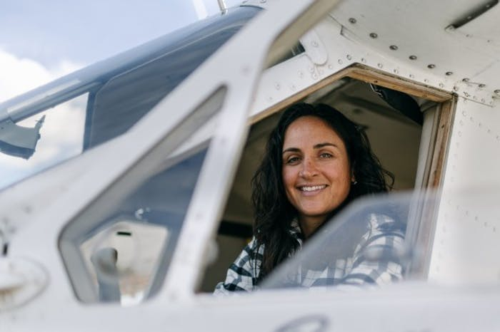 woman sits in pilot's seat of small craft