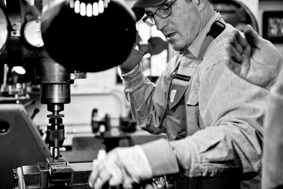 Trade Stories: Mike at Kenmore Air works on drill press at workbench in factory