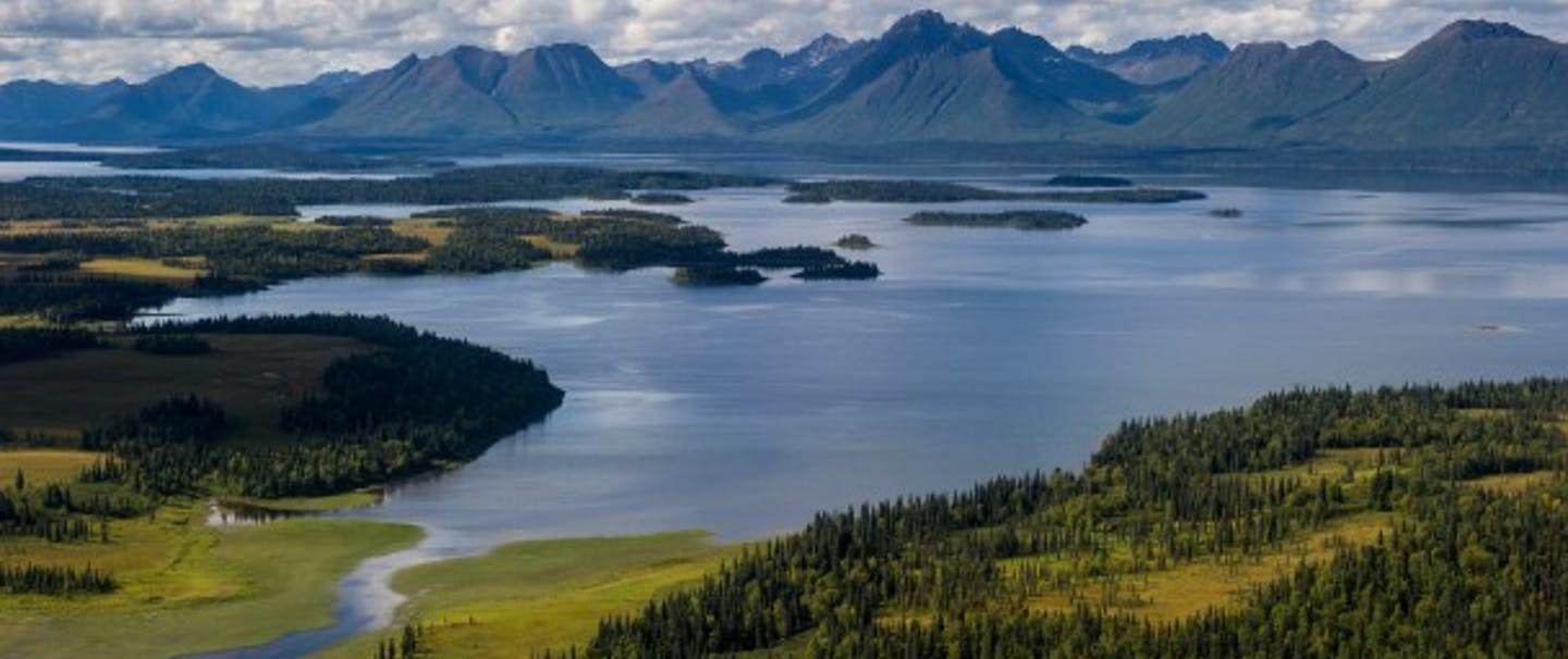 Jim Klug - Alaskan vista with large mountains in background and river opening up to large lake