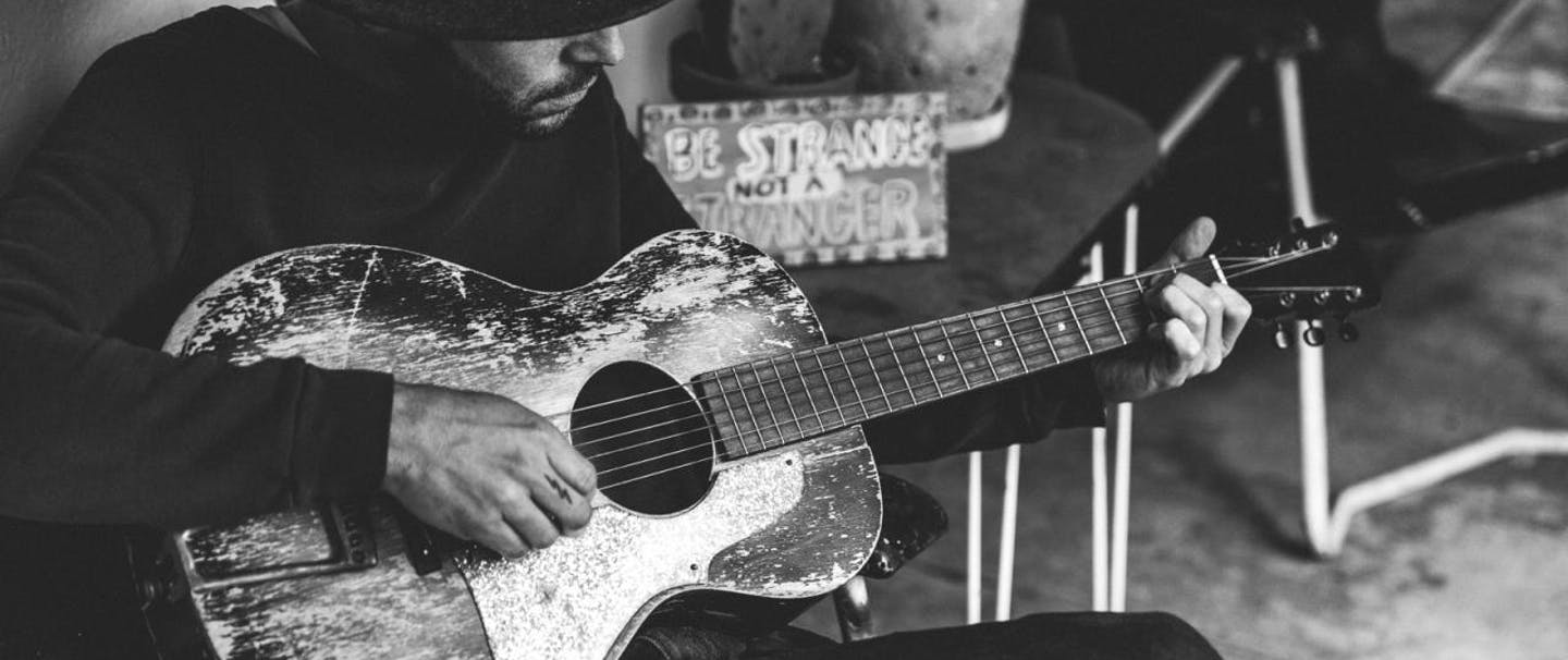 black and white image of a man sitting in a chair wearing a dark cowboy hat, pants and long sleeve shirt playing a guitar