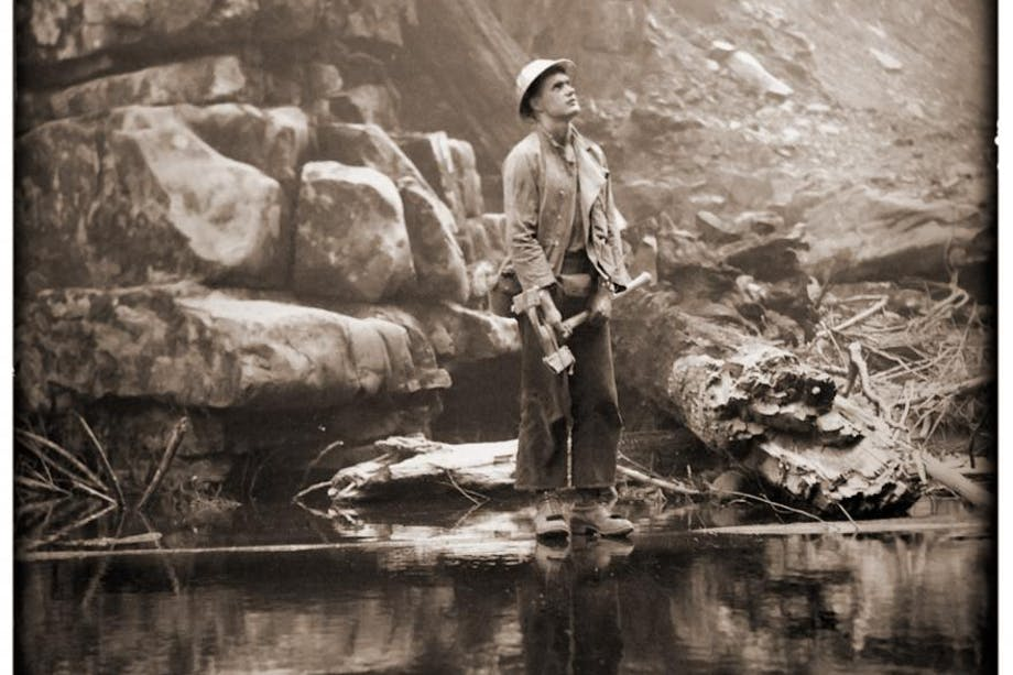 Man dwarfed by large rock face stands at foot of reflective pond gazing upward