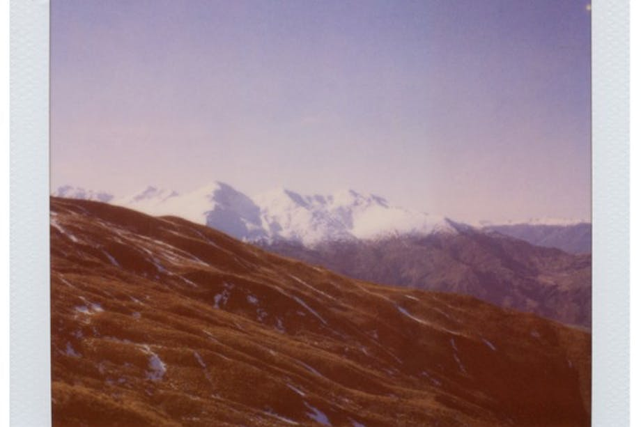 New Zealand polaroid of snowy mountains and green hills