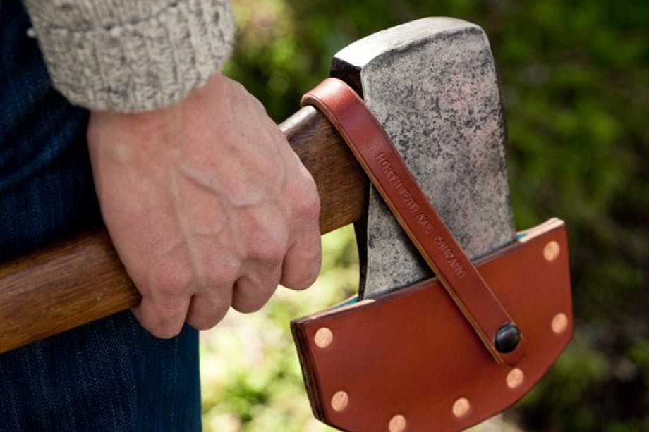 hand holds axe with leather axe blade cover