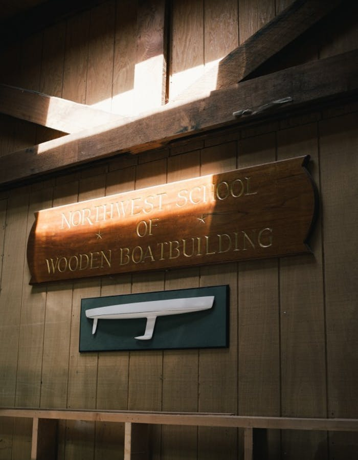 Wooden plaque on wall reads Northwest school of wooden boatbuilding