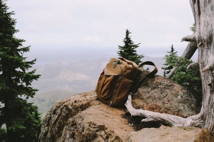 Filson backpack rests on a rock overlooking a valley