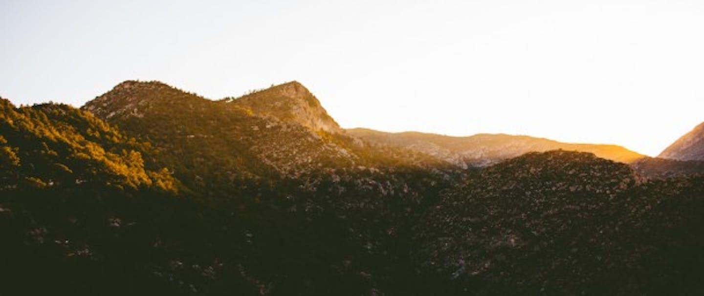 Sun breaks over mountain peak