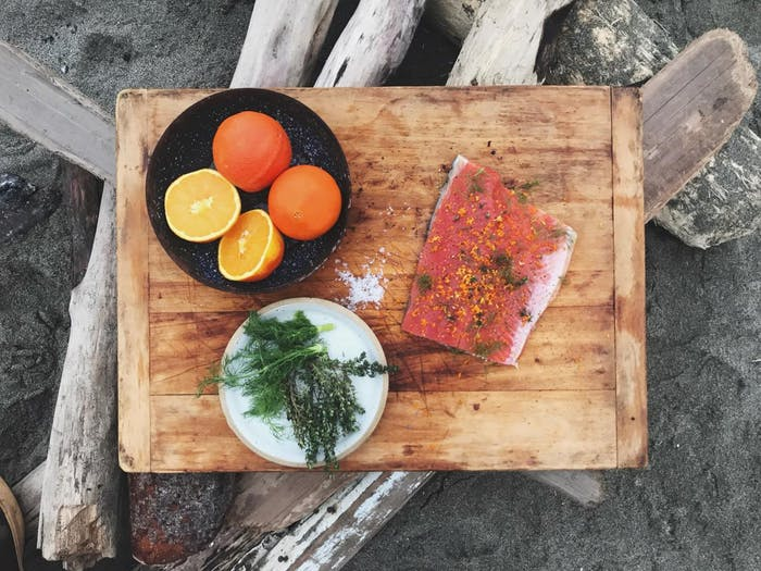 salmon filet with herbs and citrus and salt on cutting board