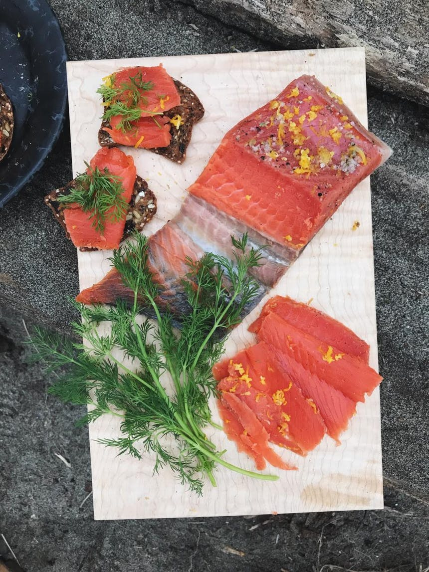 finished preparation of cured salmon on cutting board with herbs and orange zest