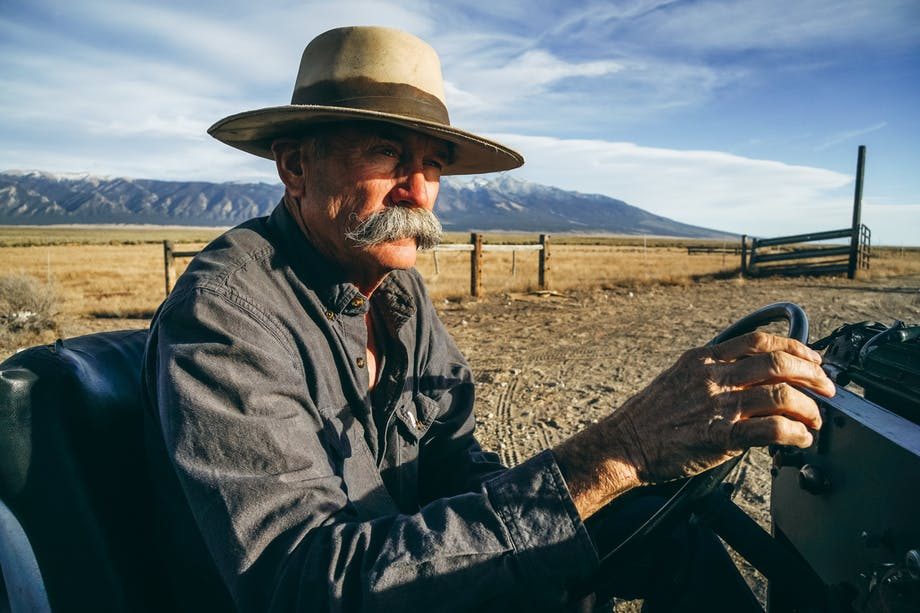 old farmer with tan flat billed hat in grassland on farm vehicle and mountain backdrop